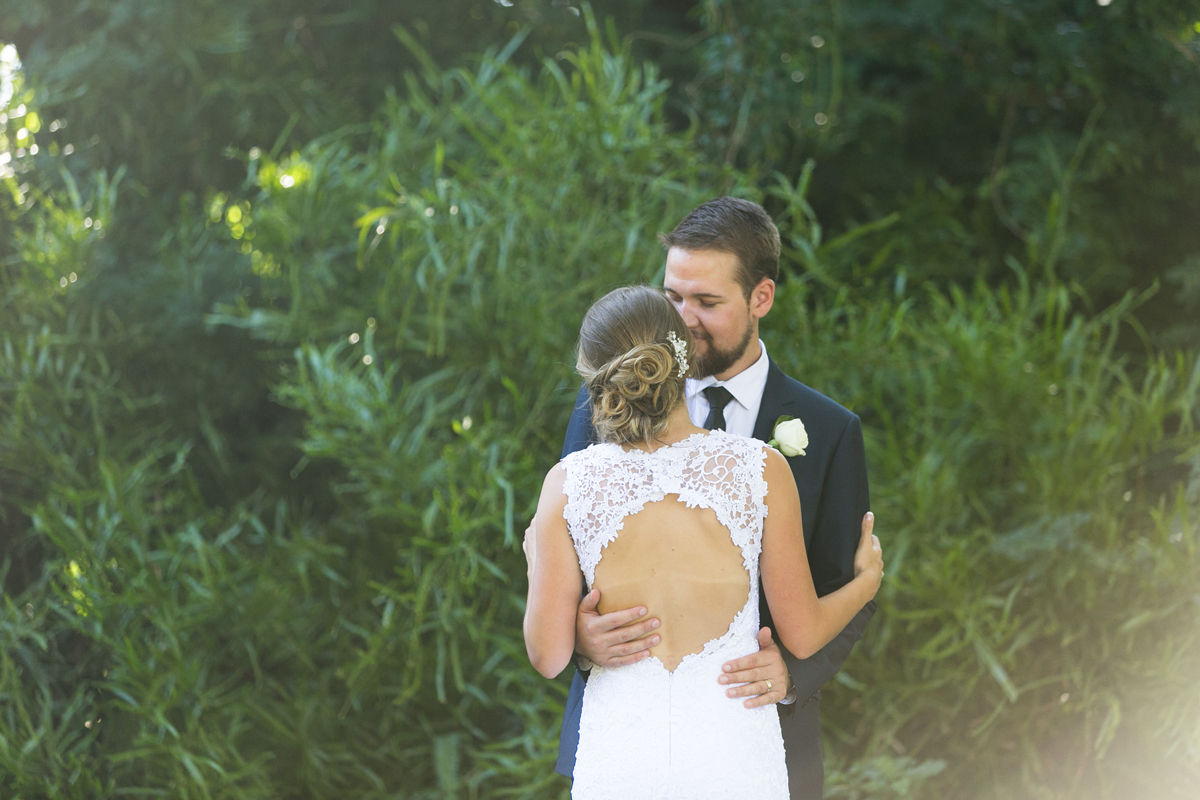 The bride and groom embrace against the backdrop of greenery with golden light streaming in from behind Tocal Homestead wedding photographer