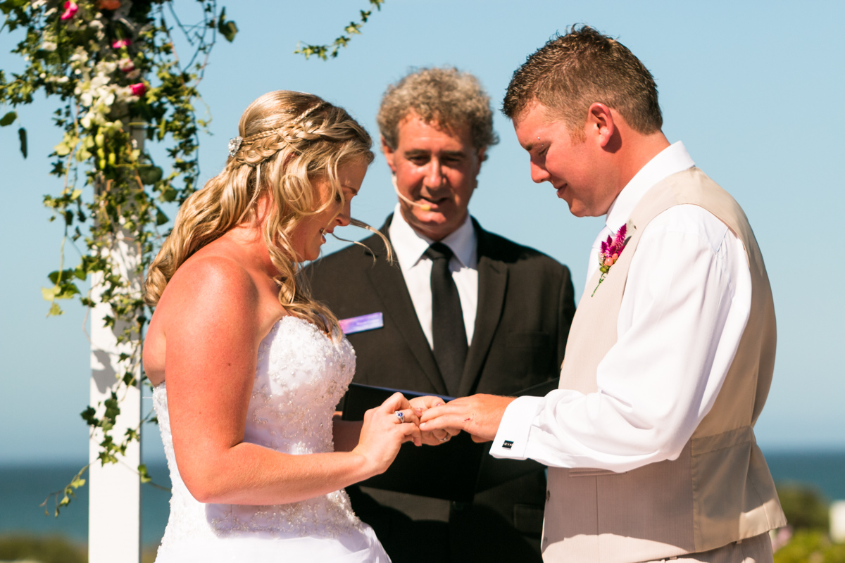 The bride puts a ring on her groom's hand during their wedding ceremony Caves Beach wedding photography