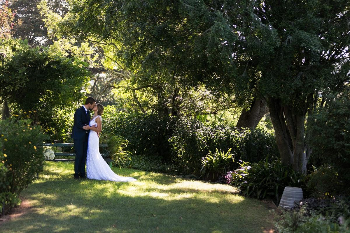 Landscape shot of the bride and groom kissing in the green grounds of Tocal Homestead wedding photographer