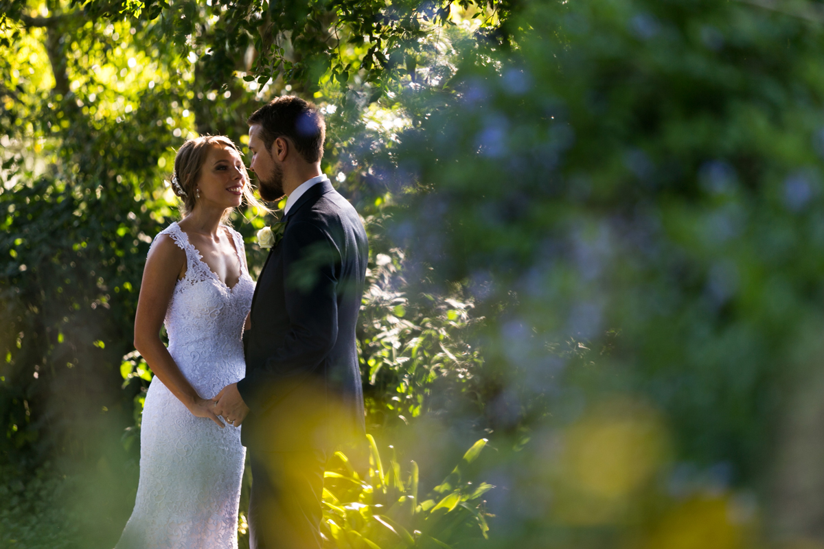 The bride and groom look into each other's eyes glimpsed behind greenery at Tocal Homestead wedding photographer