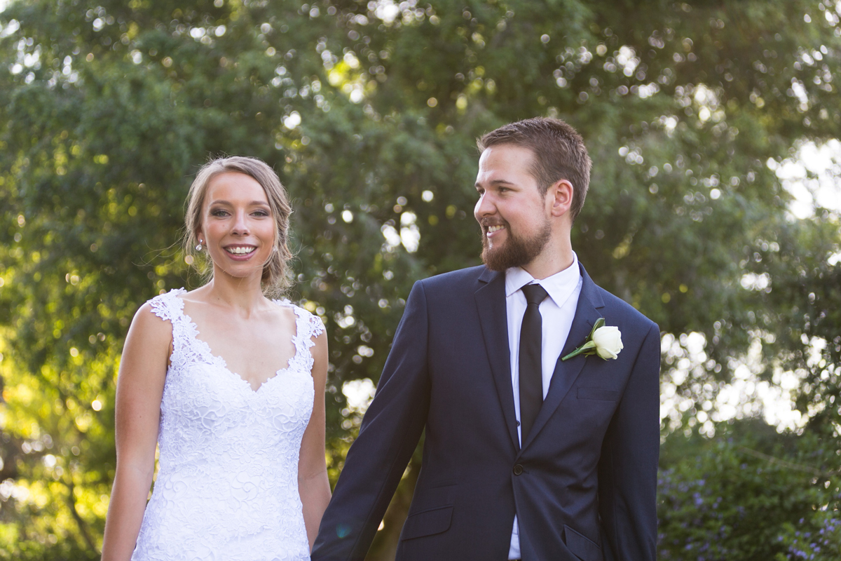 The bride and groom hold hands and walk through the grounds of Tocal Homestead wedding photographer