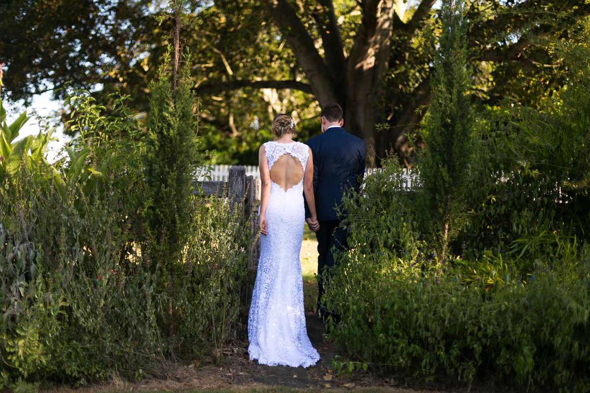 The bride and groom shot from behind walking through a rustic wooden fence surrounded by green gardens keyhole back wedding dress Tocal Homestead wedding photographer
