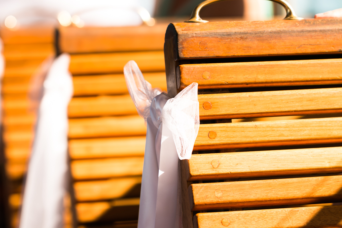 Close up detail shot of white tulle ribbons on the end of the wooden tram seats Caves Beach wedding photography