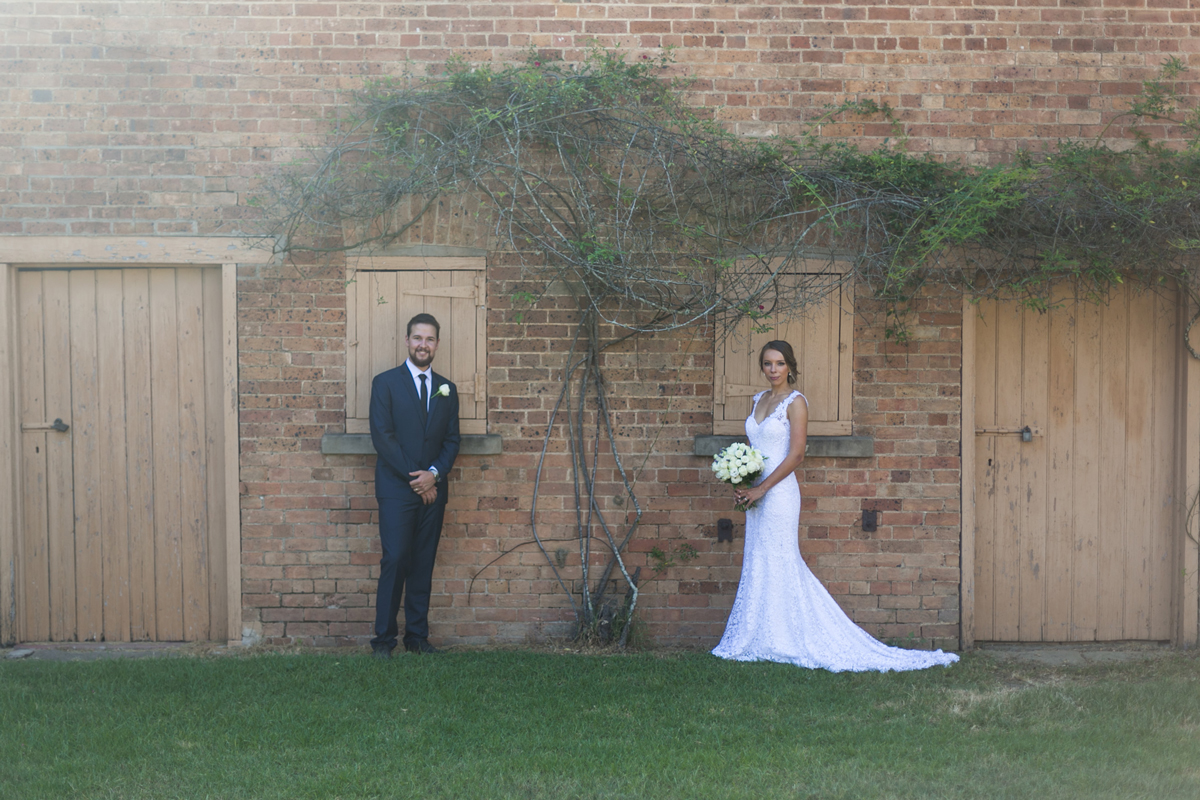 The bride and groom pose in front of a rustic brick building with a vine climbing the walls between them Tocal Homestead wedding photographer
