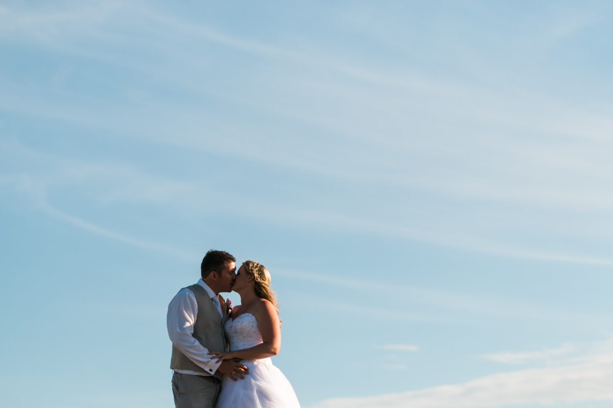 The bride and groom kiss against a backdrop of blue sky streaked with soft white clouds Caves Beach wedding photography
