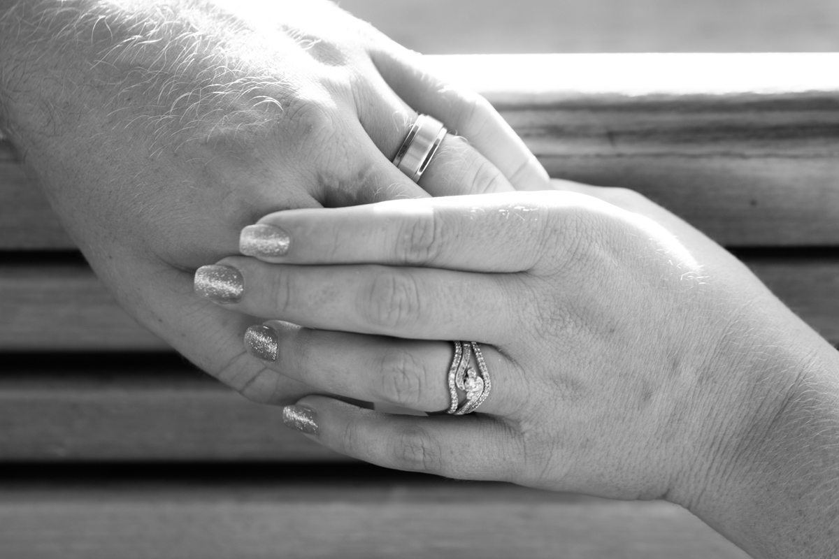 Black and white close up shot of the bride and groom's hands held together showing off their wedding bands Caves Beach wedding photography