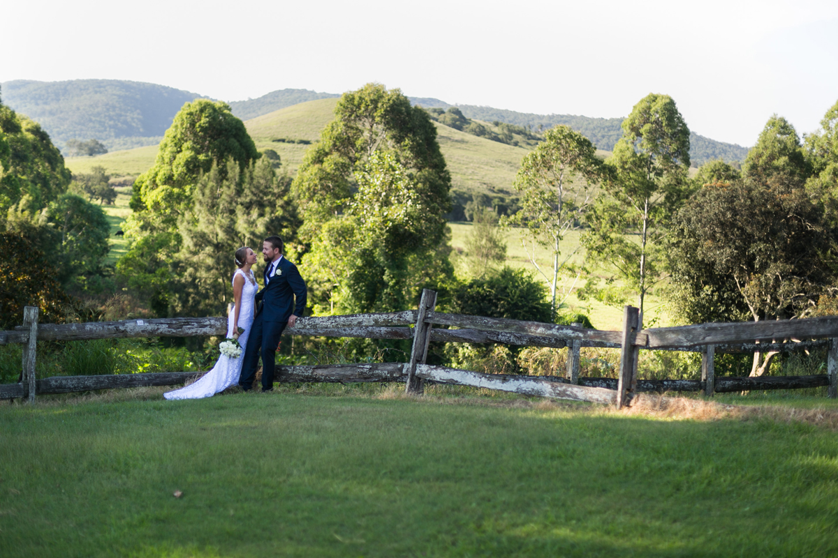 Landscape shot of the bride and groom leaning against a rustic wooden fence gazing into each other's eyes against the backdrop of rolling green fields Tocal Homestead wedding photographer