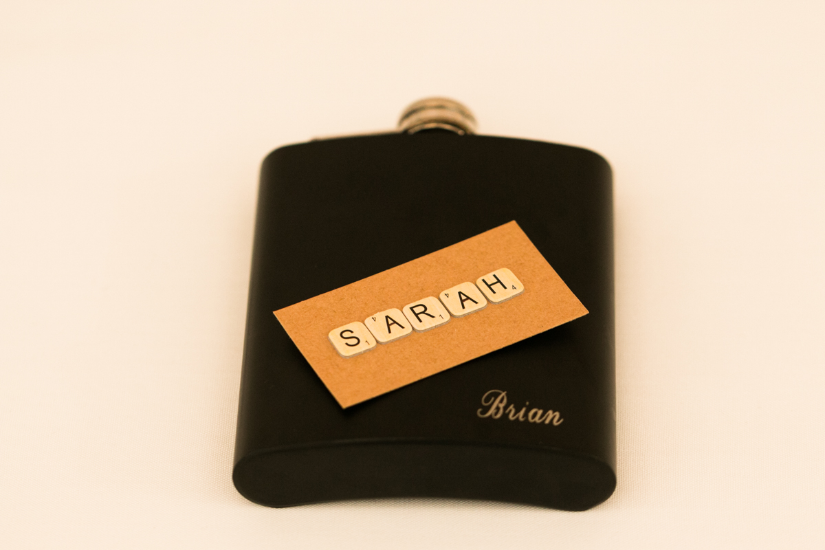 Close up shot of a black flask engraved with Brian in gold and scrabble letter place card with Sarah spelt out on a background on white linen tablecloth Caves Beach wedding photography