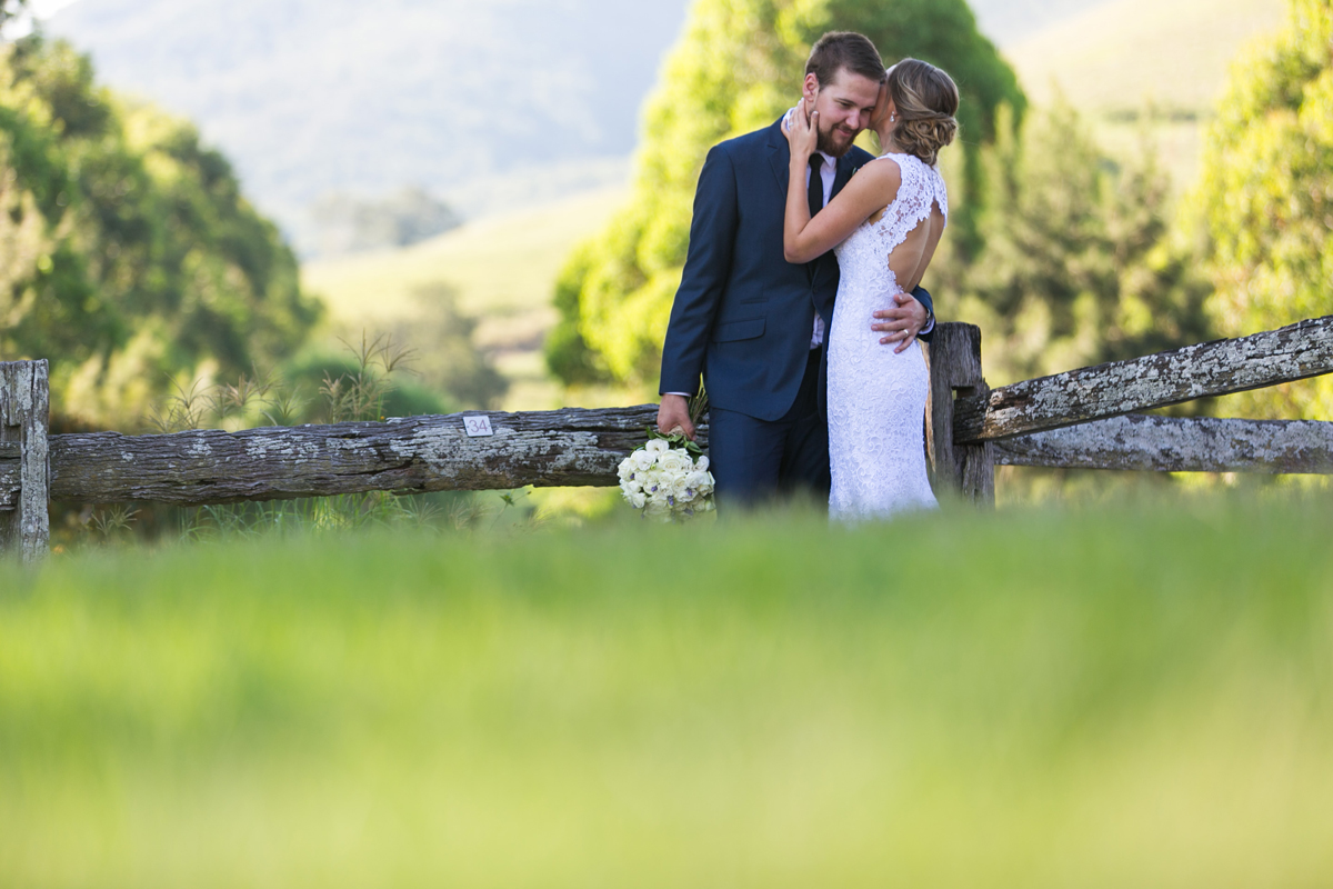 The bride whispers into the groom's ear while leaning against a rustic wooden fence in the rolling green fields with out of focus greenery in the foreground Tocal Homestead wedding photographer