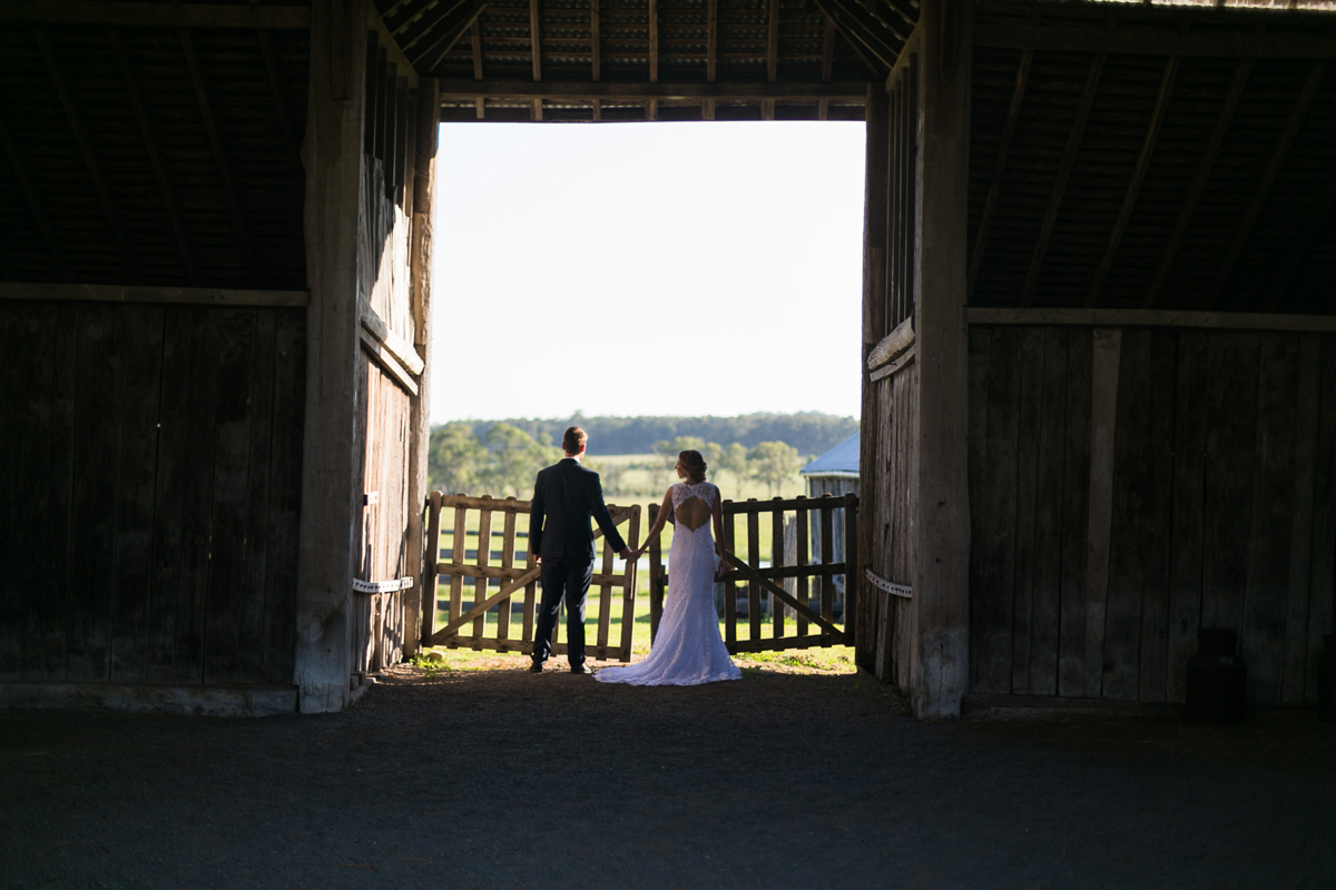 Landscape shot of the bride and groom holding hands in the doorway of a rustic wooden barn looking out over the green fields Tocal Homestead wedding photographer