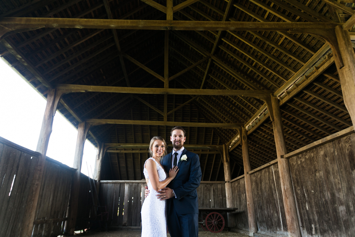 The bride an d groom stand together in the middle of a rustic wooden barn smiling into the camera Tocal Homestead wedding photographer