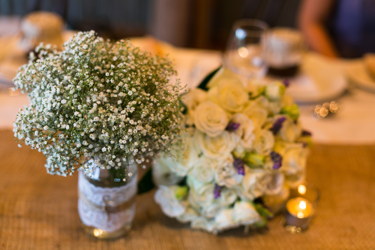 Close up detail shot of the bride's white noise bouquet and the rustic baby's breath in Mason jar table decorations at the Tocal Homestead wedding reception photographer