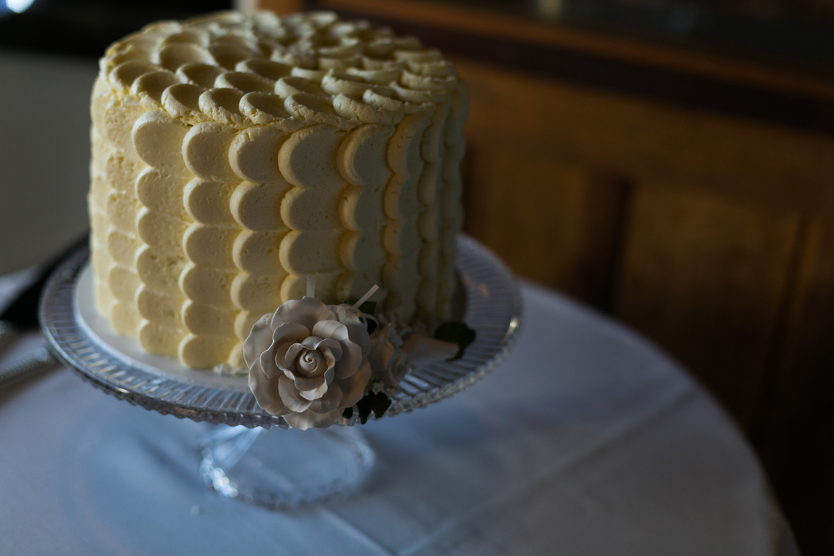 Close up shot of the simple wedding cake decorated with scalloped cream coloured buttercream icing and a single rose Tocal Homestead wedding reception photographer