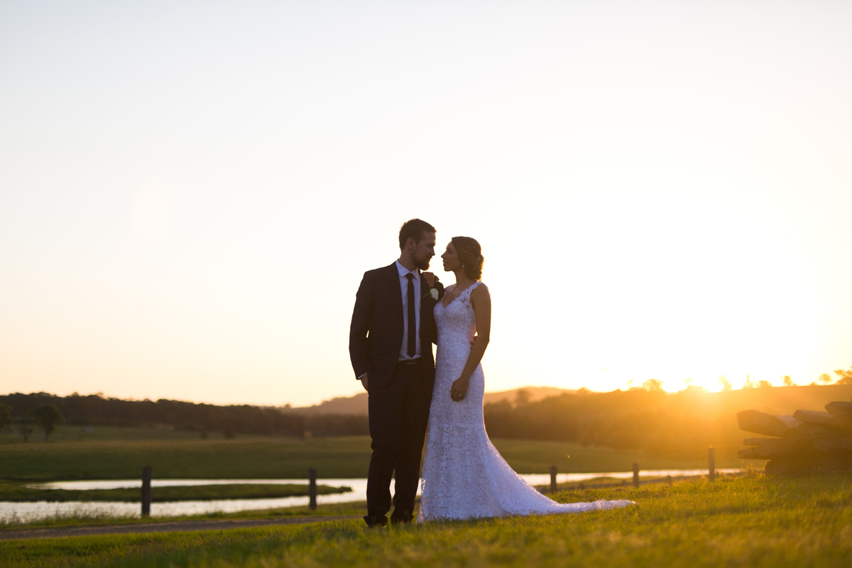 The bride and groom stand in a green field with the sunset behind them Tocal Homestead wedding photographer