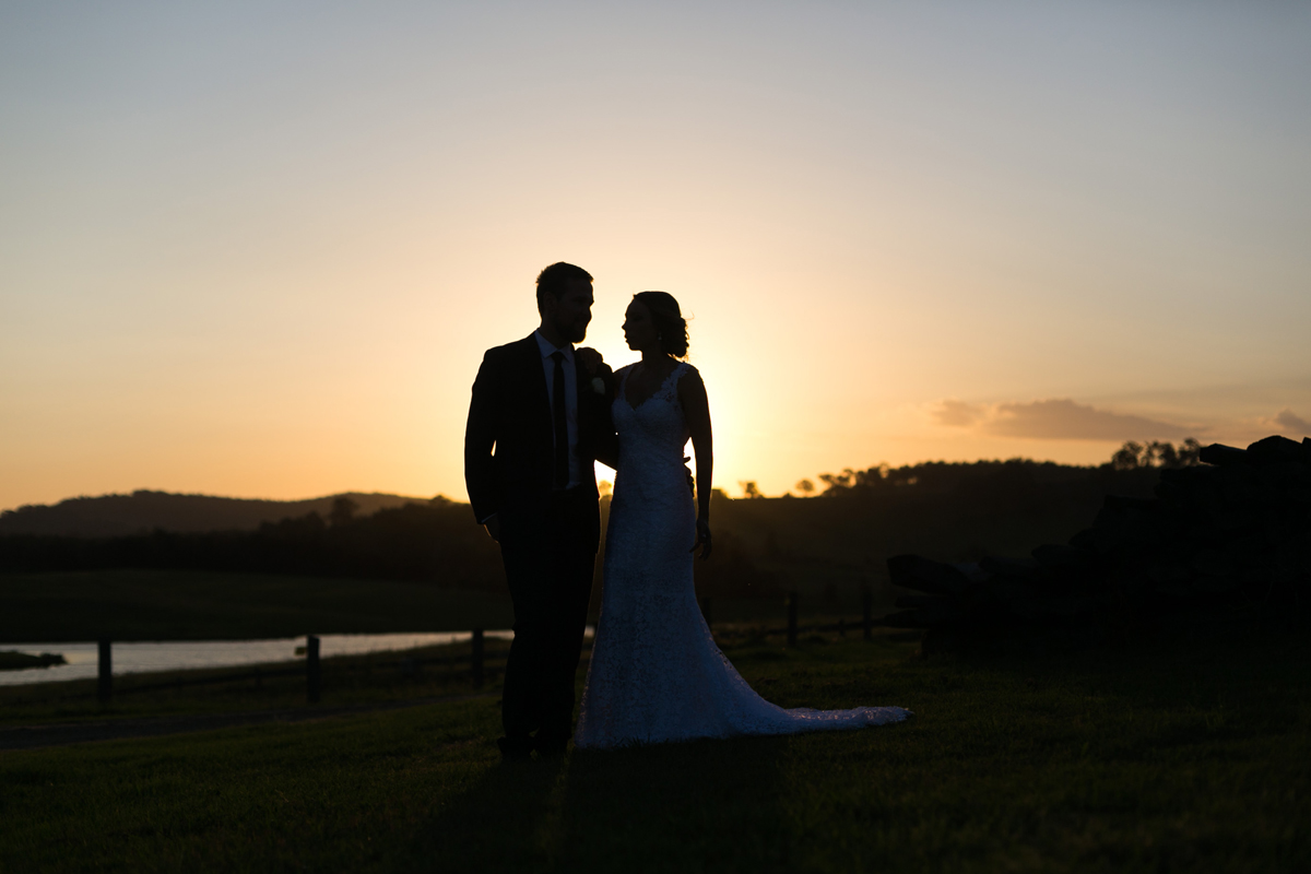 The bride and groom stand together silhouetted against the sunset in a field Tocal Homestead wedding photographer
