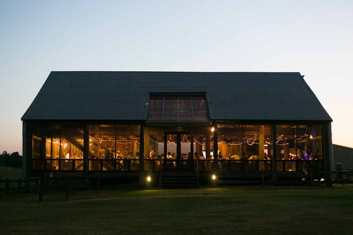 The reception venture at dusk lit with golden light and fairy lights shot from the outside Tocal Homestead wedding photographer